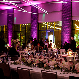 wedding reception tables with purple uplighting